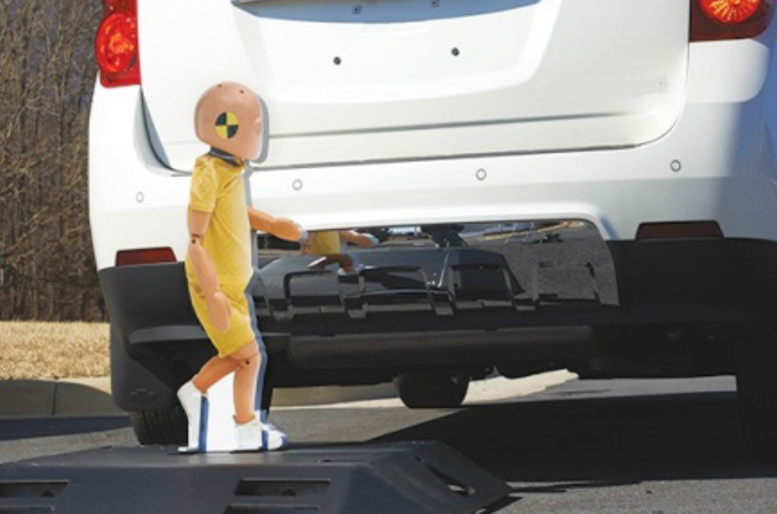 Child pedestrian dummy wanders behind a car.