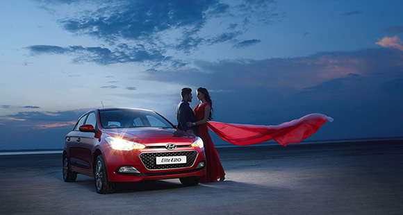 A couple standing next to red Elite i20 headlight on the beach in the evening