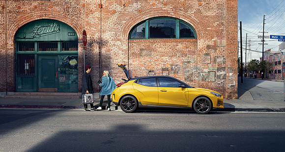 Peoples and side view of yellow veloster parking on the road