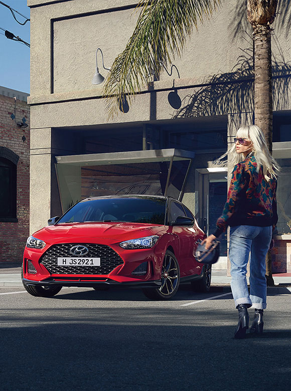 Red Veloster parked on the road beside blond woman
