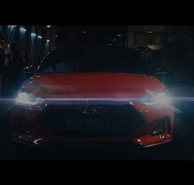 Front view of the red Veloster turn on its headlights.