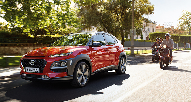 left side front view of red kona driving on the road
