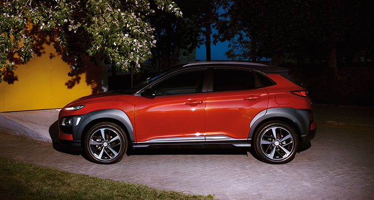 left side view of red kona parked on the road