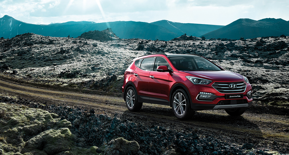 Side front view of red Santa Fe driving on the unpaved road with wild nature behind