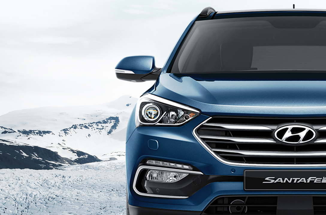 Front view of blue Santa Fe with snowy mountain background