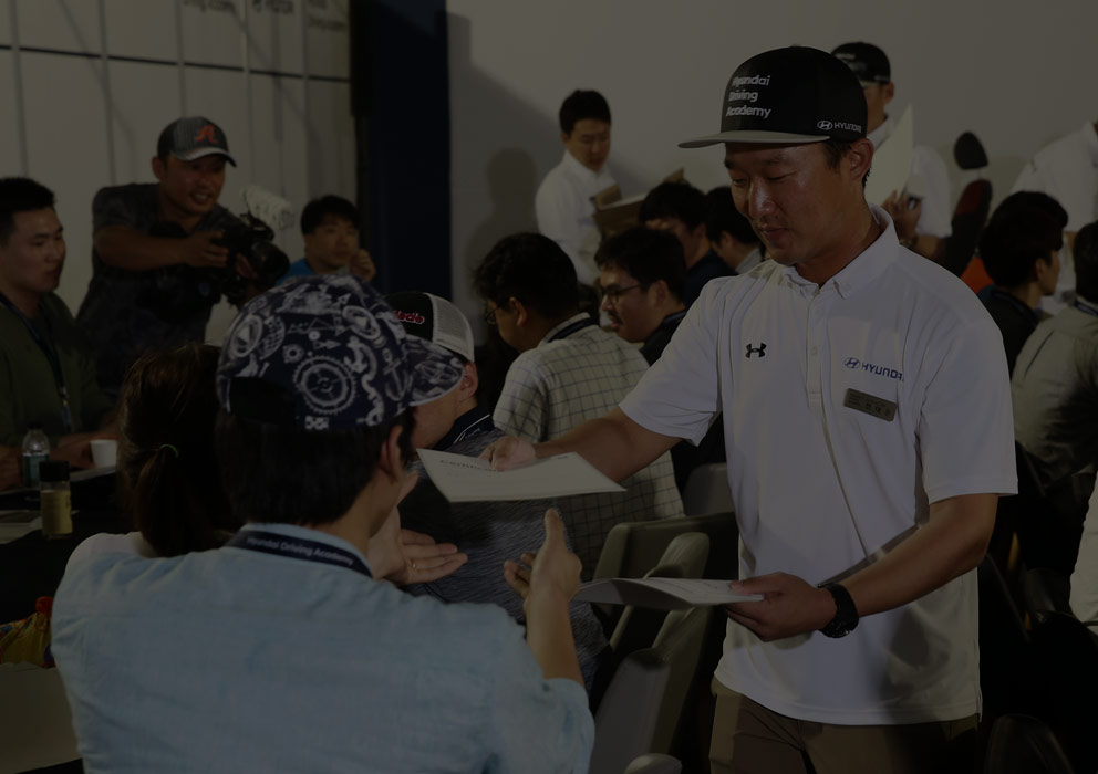 coach awards the completion certificate of Hyundai driving academy to drivers