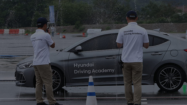 two coaches guide the grey racing car on the wet training ground of hyundai driving academy