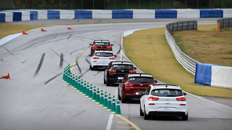 rear view of five racing cars are running on the track in race class