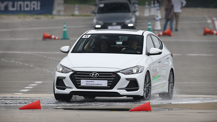 front view of white racing car in a safety class on the wet training road