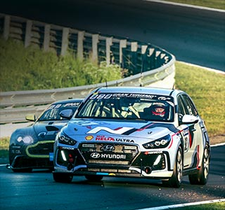 two cars are running at a race track of the nürburgring