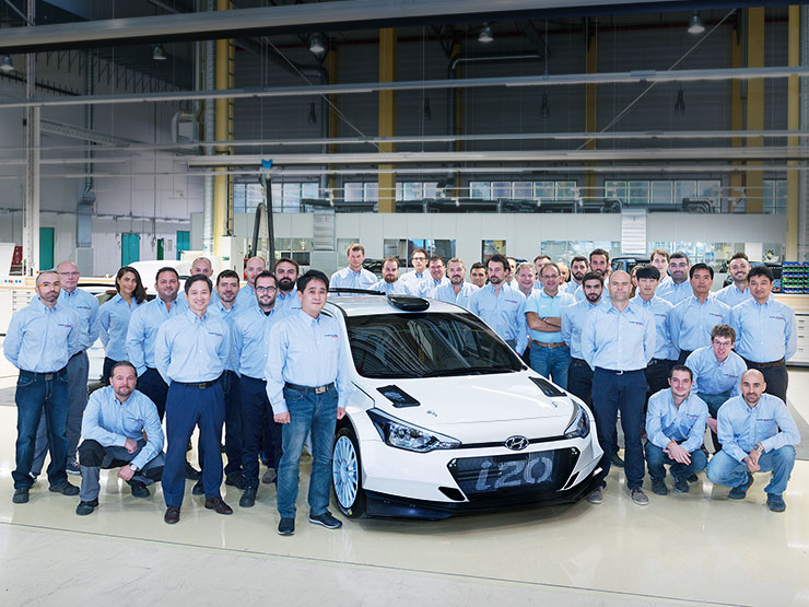 the group photo of the engineers with i20 R5 in the workshop