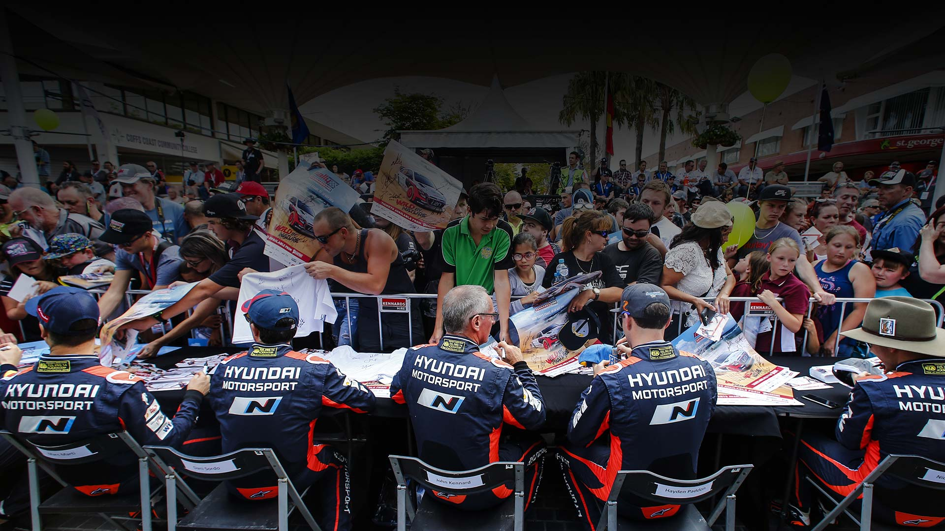 rear view of motorsport crews in an autograph meeting