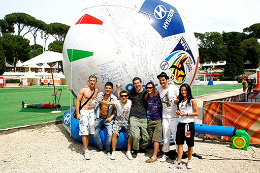 Fans are standing in front of the 2010 FIFA World Cup gigantic four-meter height football
