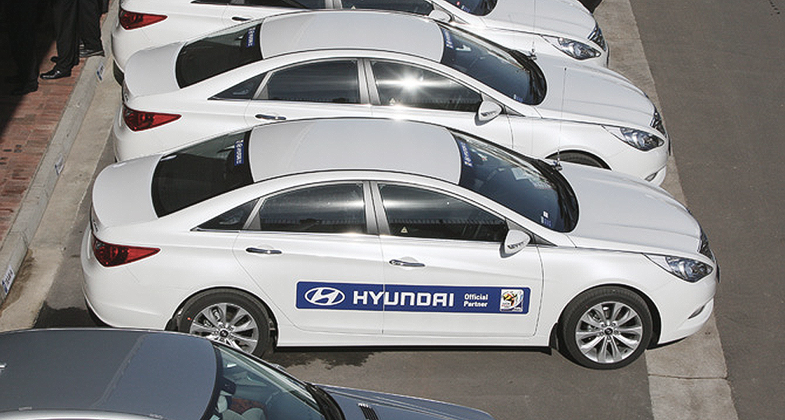 Hyundai composite logo shown on side of white vehicles parked in outdoor